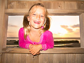 Young girl smiling through window at sunset