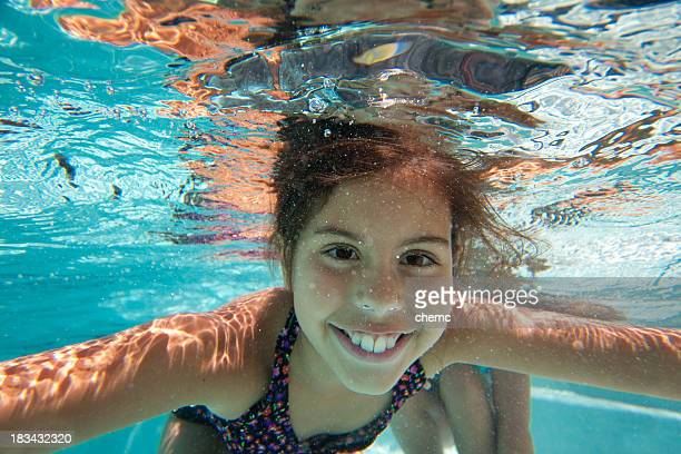 Young girl smiling underwater in a swimming pool