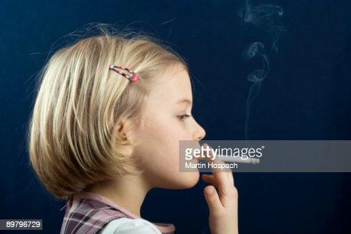 A young girl smoking a cigarette : Stock Photo