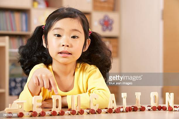 A young girl spelling the word education with her letter train.