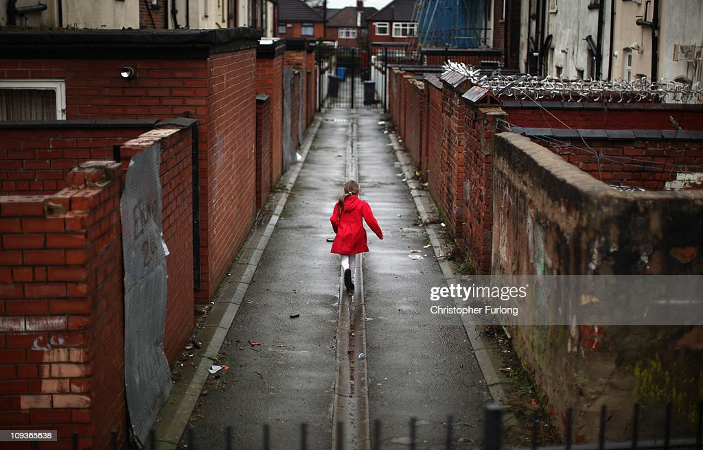 A young girl spends the half term school holiday playing in an an alleyway in the Gorton area of Manchester on February 23, 2011 in Manchester, England. Charity 'Save the Children' today announced that up to 1.6 million children in the UK are living in poverty, with the Manchester area of Gorton and Tower Hamlets in London topping the survey at 27% of children in those areas living in poverty. The report highlighted one case in Gorton where 11 people - three adults and 8 children - lived in a two bedroomed terraced house.