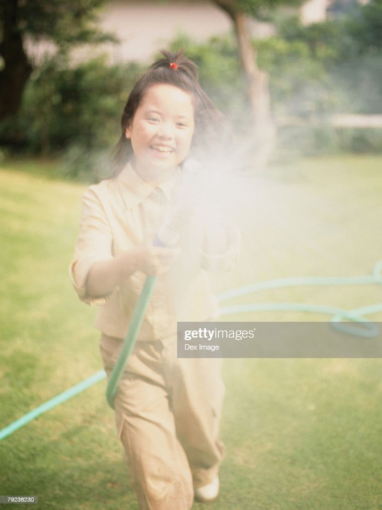 Young girl spraying water with hose : Stock Photo