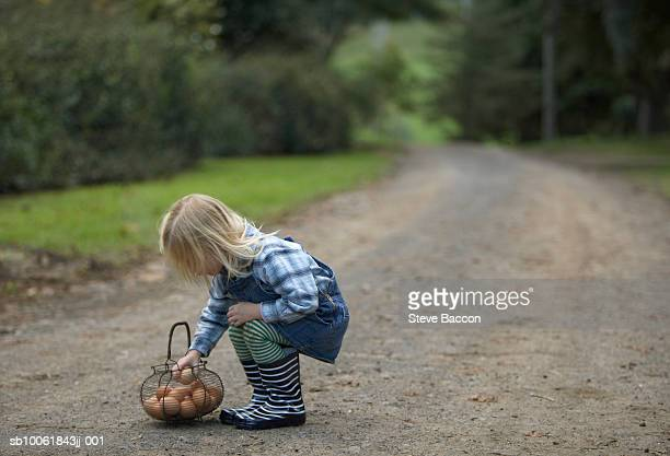 Young girl (3-4) squatting on road by basket with eggs, side view
