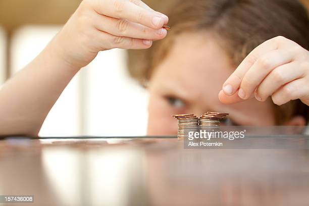 Young girl stacking coins on a tabletop