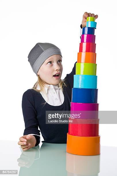 Young girl stacking many colorful round boxes