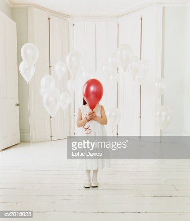 Young Girl Standing Behind a Red Balloon in a White Room : Stock Photo