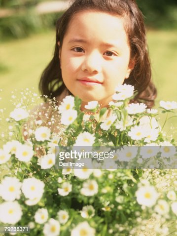 Young girl standing behind flowers : Stock Photo