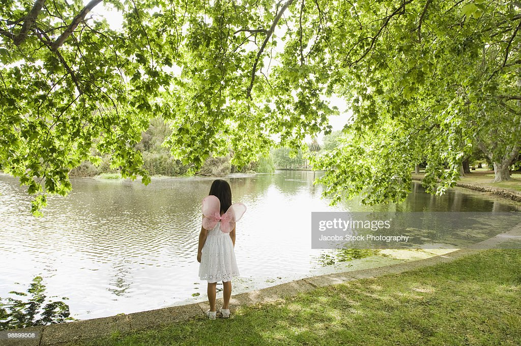Young Girl Standing by Lake in Park : Stock Photo