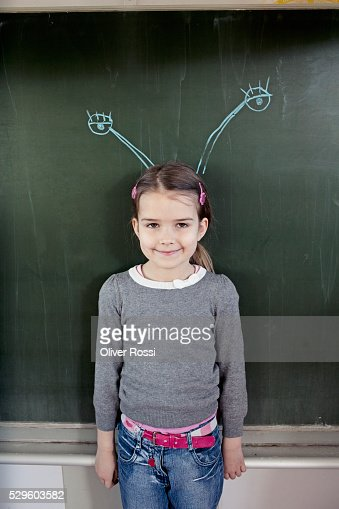 Young girl (6-7) standing in front of blackboard with insect feelers drawn on it : Stockfoto