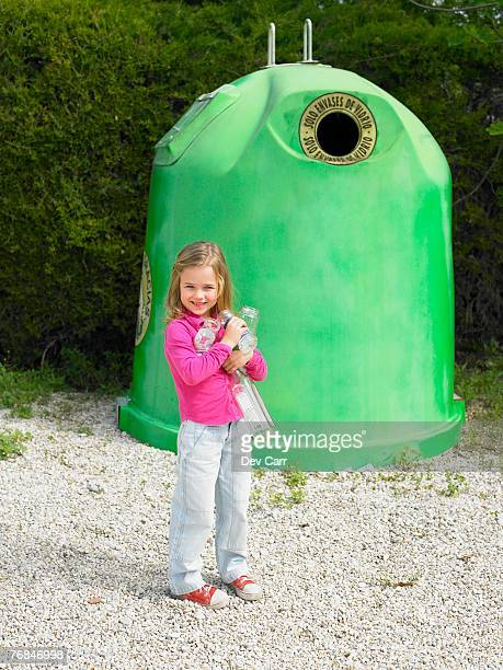 Young girl (5-7) standing in front of recycling bin holding glass bottles, Alicante, Spain,