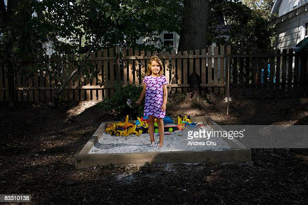 Young girl standing in sandbox holding flowers.