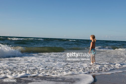 Young Girl Standing On Beach In - 116.4KB