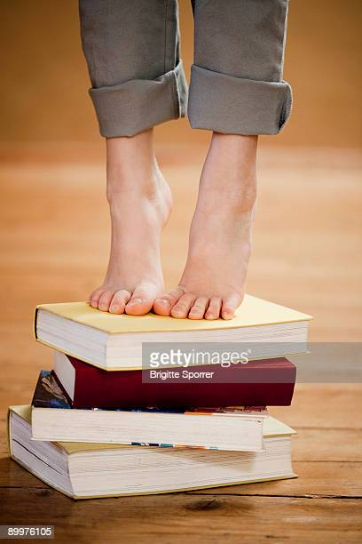 young girl standing on books