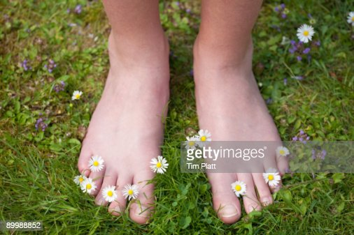 Young girl standing on grass with bare feet. : Stock Photo