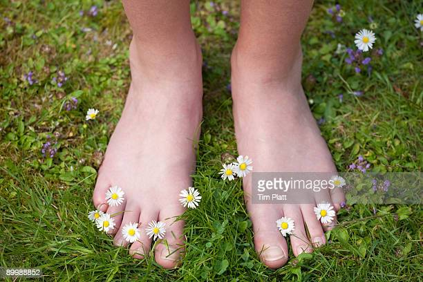 Young girl standing on grass with bare feet.