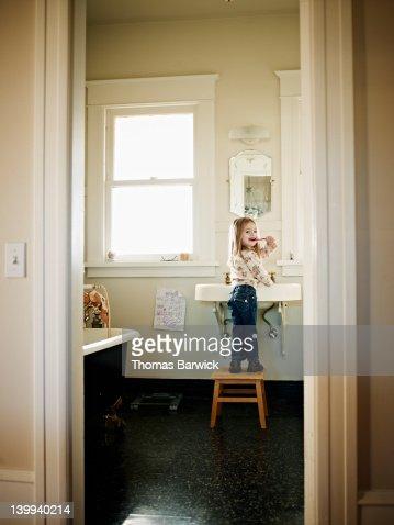 Young girl standing on stool brushing teeth : Stock Photo