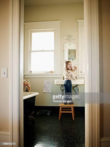 Young girl standing on stool brushing teeth