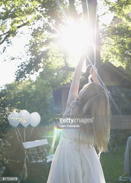 Young girl standing outdoors holding balloons