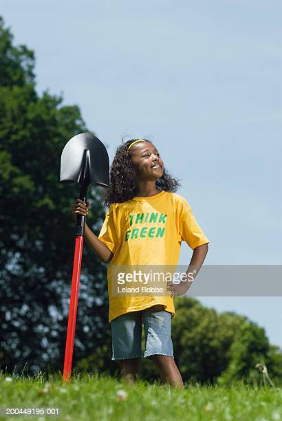 Young girl (8-10) standing with shovel looking away, smiling