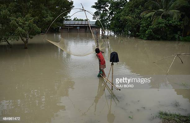 A young girl stands alongside a fishing net in front of her school which is partially submerged at the flood affected Mayong village in the Morigaon...