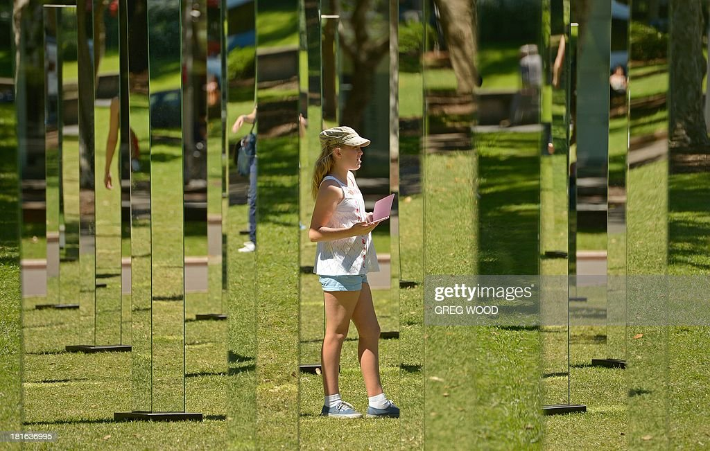 A young girl (C) stands alongside a maze of mirrors that make up the installation 'Field' from Art & About Sydney on September 23, 2013. Field, developed by New Zealand architecture collective 'Out of the Dark', is a mesmerising set of mirrors on 81 posts designed to be a place of literal reflection where the perspective is ever-changing, encouraging curious passers-by. AFP PHOTO / Greg WOOD CAPTION