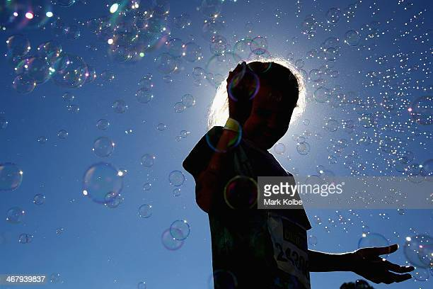 A young girl stands amongst bubbles near the finish line of the Color Run at Sydney Olympic Park on February 9 2014 in Sydney Australia