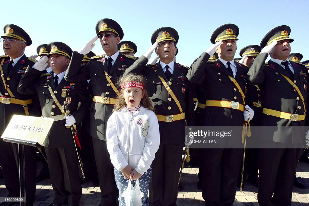 A young girl stands at attention in front of Turkish officers stand at attention during the celebration ceremony of Turkey's 90th Republic Day on October 29, 2013, marking the day on which founder Mustafa Kemal Ataturk declared the Turkish Republic in 1923, at Ataturk's Anitkabir mausoleum in capital Ankara. AFP PHOTO/ADEM ALTAN