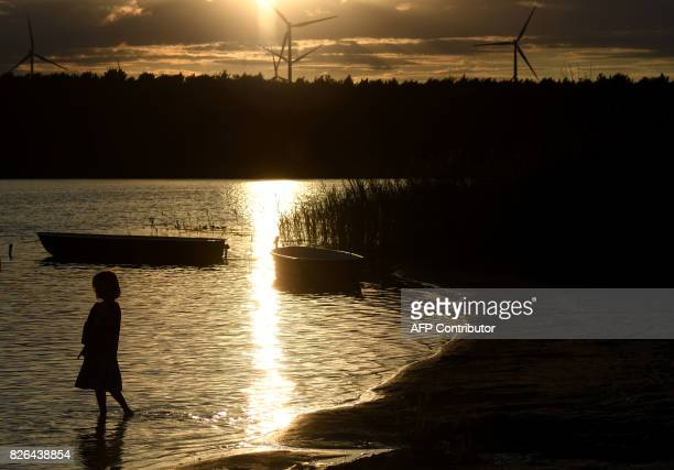 A young girl stands at the shore of the small lake in the Spreewald area near Cottbus eastern Germany during sunset after a hot summer day with...
