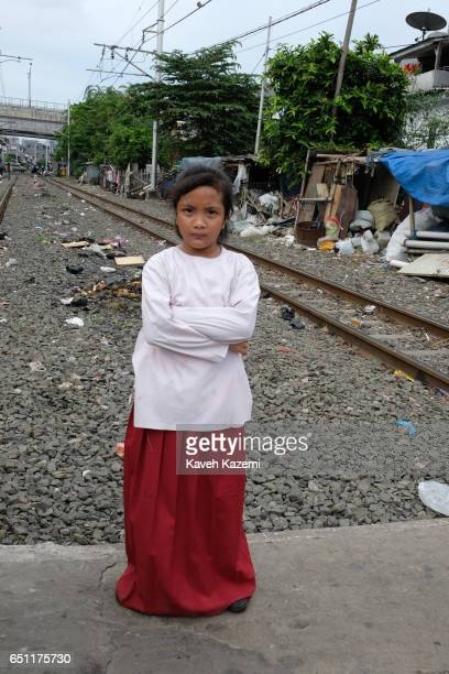A young girl stands between the railroad tracks in Kota City on November 25 2016 in Jakarta Indonesia The slum dwellers have been living on both...