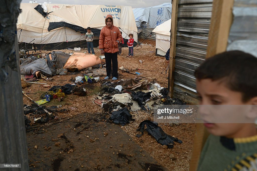 A young girl stands in a burnt out tent as Syrian refugees go about their daily business in the Za'atari refugee camp on February 1, 2013 in Za'atari, Jordan. Record numbers of refugees are fleeing the violence and bombings in Syria to cross the borders to safety in northern Jordan and overwhelming the Za'atari camp. The Jordanian government are appealing for help with the influx of refugees as they struggle to cope with the sheer numbers arriving in the country.