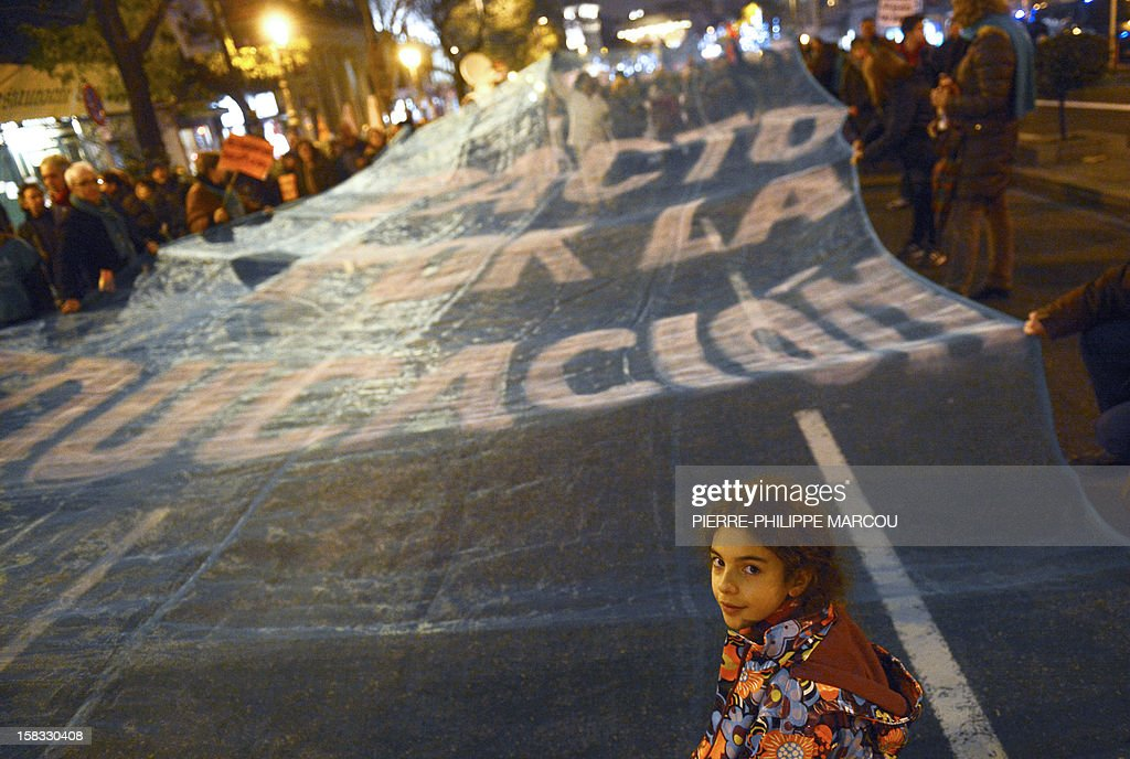 A young girl stands in front of a giant banner reading 'Agreement for the education' during a protest against government's austerity reforms and cuts in Madrid on December 13, 2012. Public spending on education has been cut by more than a billion euros this year compared with 2011, and public schools employed nearly 3,000 fewer teachers during the 2011-12 academic year, according to the education ministry.