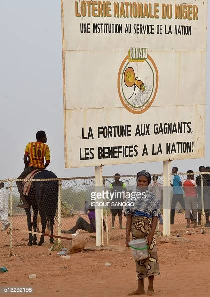 A young girl stands in front of a placard which translates as 'National lottery of Niger An instution for the nation Fortune for the winners befenits...