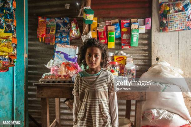 A young girl stands in front of a products in a small shop run by her mother in a lowincome area of Masaya Nicaragua on 19 October 2011