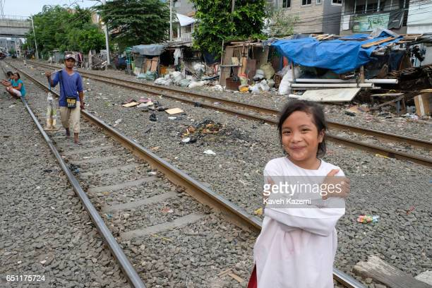 A young girl stands on the rairoad track in Kota City on November 25 2016 in Jakarta Indonesia The slum dwellers have been living on both sides of...