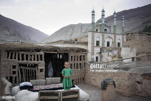A young girl stands on the roof of the family house on June 11 2007 about 70 kilometers east of Turpan in Tuyoq China The ancient village is close to...