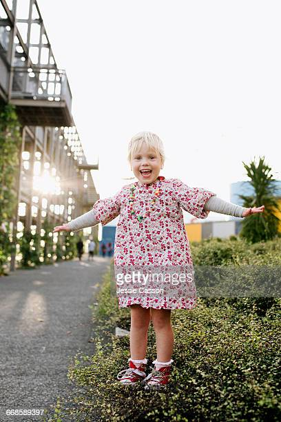 Young girl stands on wall