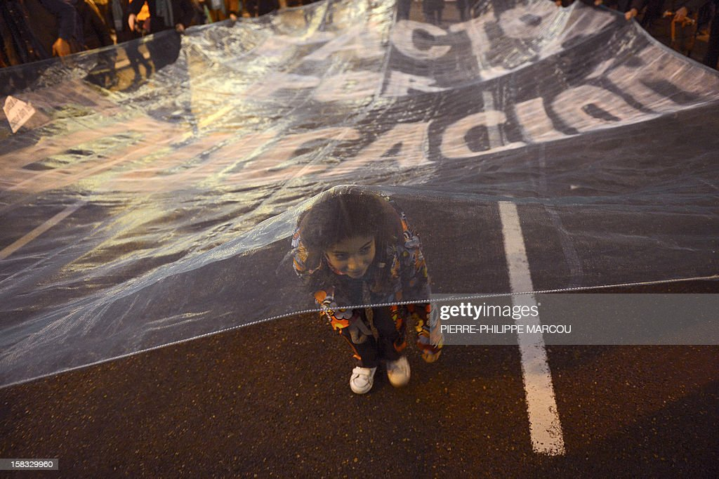 A young girl stands under a giant banner during a protest against government's austerity reforms and cuts in Madrid on December 13, 2012. Public spending on education has been cut by more than a billion euros this year compared with 2011, and public schools employed nearly 3,000 fewer teachers during the 2011-12 academic year, according to the education ministry. AFP PHOTO/ PIERRE-PHILIPPE MARCOU