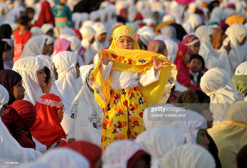 A young girl stands up as Indonesian Muslims take part in special morning prayers near the Bajrah Sandhi monument in Denpasar on Indonesia's island of Bali on August 8, 2013. Muslims around the world will celebrate Eid al-Fitr this week, marking the end of holiest month of Ramadan during which followers are required to abstain from food, drink and sex from dawn to dusk.