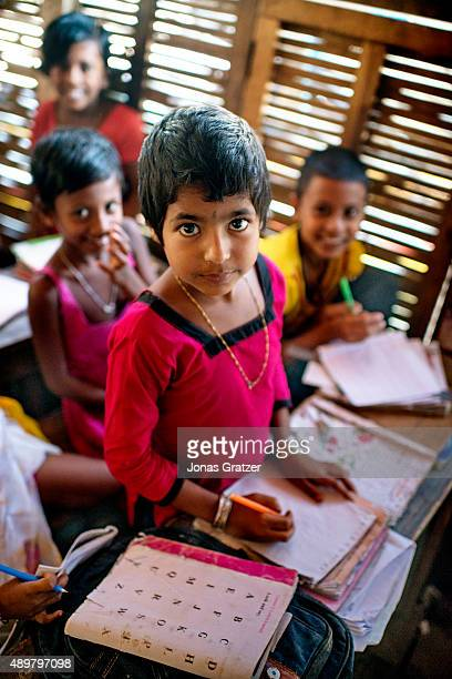 A young girl stands up to present her schoolwork to the other students on the solar powered floating boat school Shidhulai Swanirvar Sangstha has...