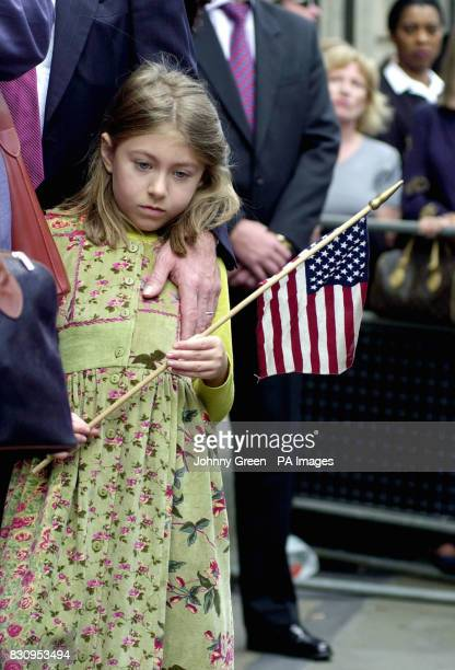 A young girl stands with an American stars and stripes flag outside St Paul's Cathedral in the City of London White rose petals representing those...