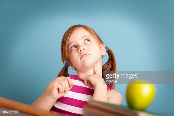 Jeune fille étudiant assis au bureau de l'école de la pensée