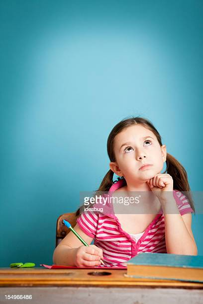 Jeune fille étudiant de la pensée et d'un bureau à l'école