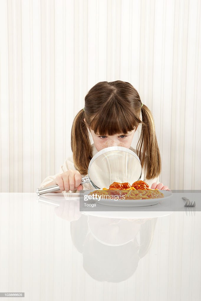 Young girl studying food with magnifying glass : Stock Photo