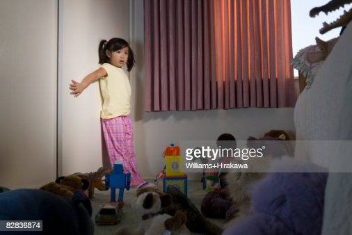 Young girl surrounded by toys looking scared : Stock Photo