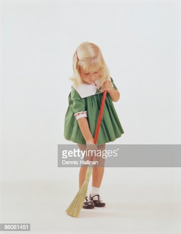 Young Girl Sweeping Floor with Broom : Stock Photo