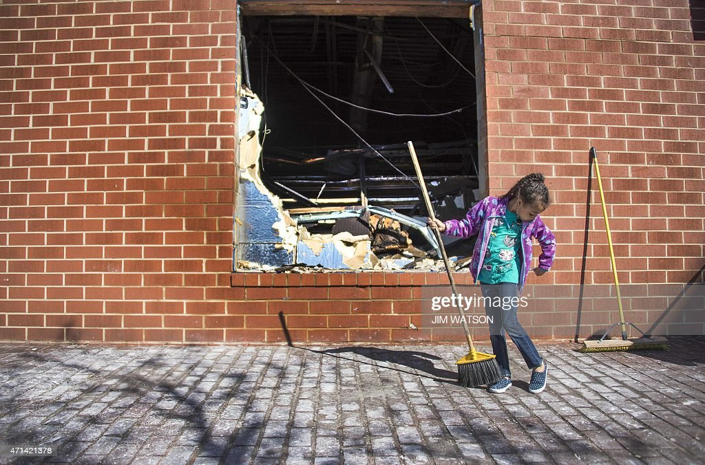 A young girl sweeps up the area outside the CVS Pharmacy in Baltimore Maryland April 28 that was set on fire during rioting last night Riot police...