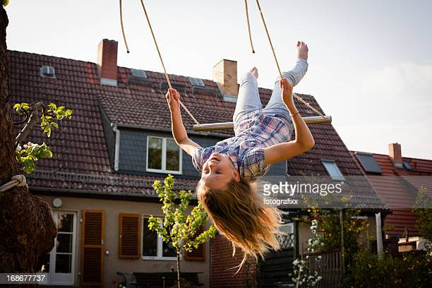 A young girl swinging in the backyard