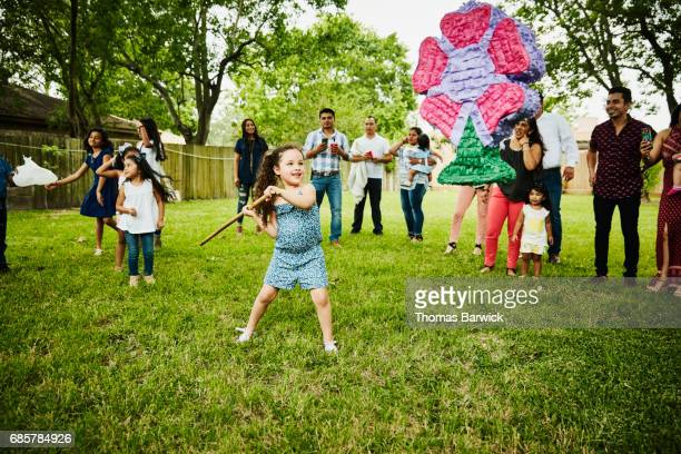 Young girl swinging stick at pinata during family birthday party in backyard