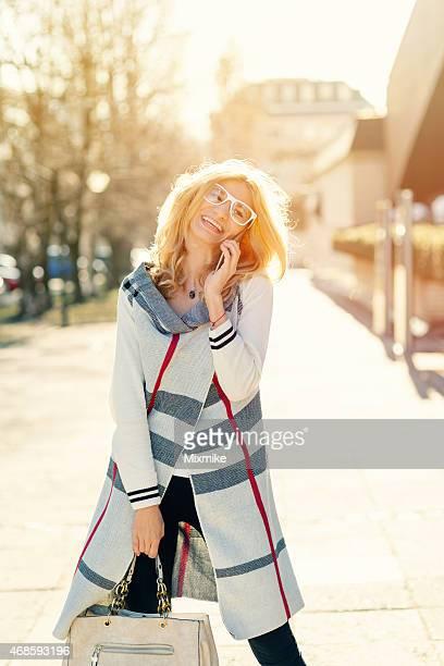 Jeune fille parlant sur le téléphone portable dans la rue