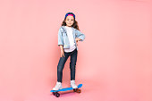 Young female teen youth trends studio skater with skateboard